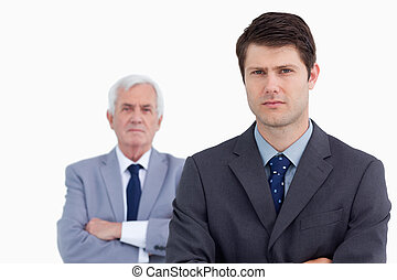 Close up of serious businessman with his mentor behind him