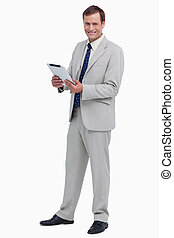 Smiling businessman with his tablet computer against a white...