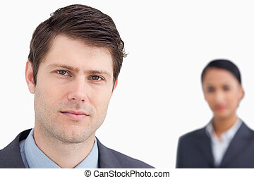 Close up of young salesman with colleague behind him