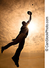 The silhouette of baseball player jumping into air to make...