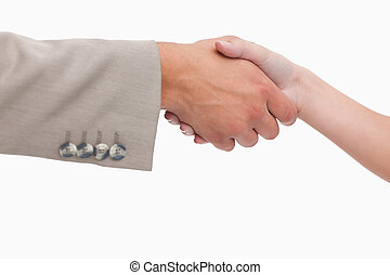 Close up of female and male hand shaking against a white...