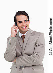 Smiling salesman on his cellphone against a white background