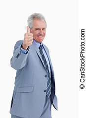 Mature tradesman giving his thumb up against a white...