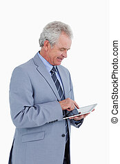 Side view of smiling mature tradesman using tablet computer...