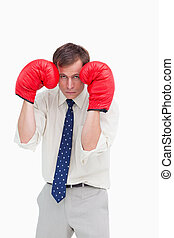 Businessman with boxing gloves taking cover against a white...