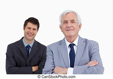 Close up of mature businessman with folded arms and colleague behind him against a white background
