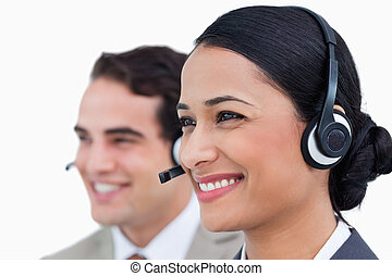 Close up side view of smiling call center agents against a...