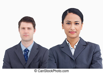 Close up of confident saleswoman with colleague behind her