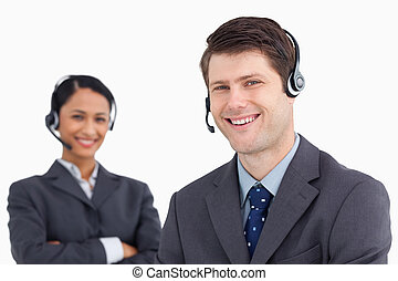 Close up of smiling male call center agent with colleague behind him against a white background