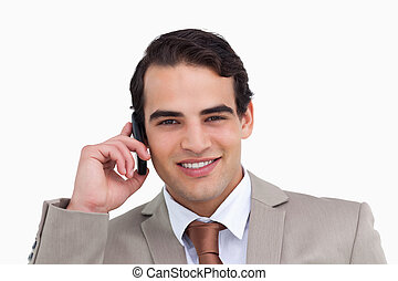 Close up of salesman on his cellphone against a white...