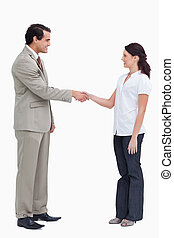 Side view of business people shaking hands against a white...