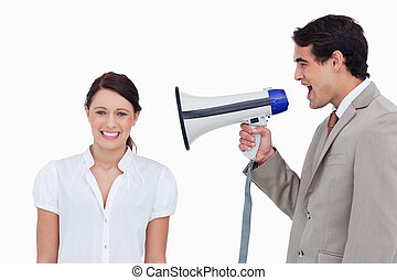Salesman yelling at colleague with megaphone against a white...