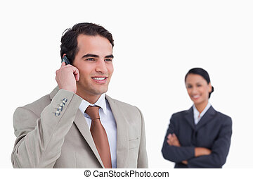 Smiling salesman on his mobile phone with colleague behind him