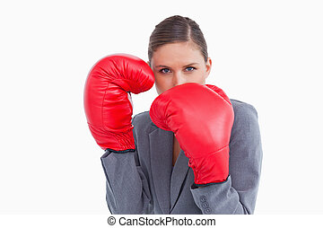 Tradeswoman with boxing gloves in defensive position against...