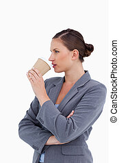 Side view of tradeswoman taking a sip out of her paper cup...