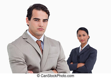 Serious salesman with colleague behind him