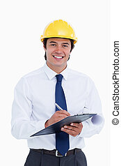 Smiling male architect with clipboard and pen against a...