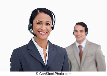 Smiling telephone support employee with colleague behind her...