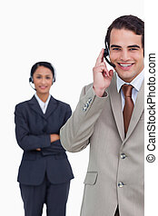 Smiling hotline employee with colleague behind him against a...