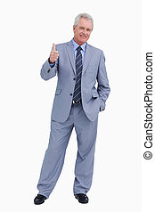 Smiling mature tradesman giving thumb up against a white...