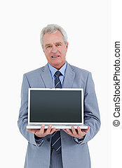 Mature tradesman presenting screen of his laptop against a...