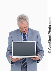 Mature tradesman holding and looking at laptop screen...