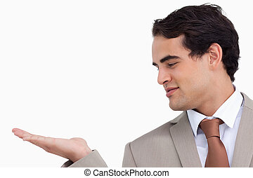 Close up of salesman looking at his palm against a white...