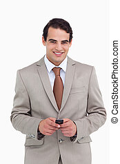Smiling salesman holding his cellphone