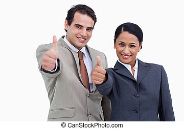 Smiling salespeople giving thumbs up against a white...