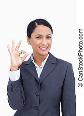 Close up of smiling saleswoman giving approval against a...