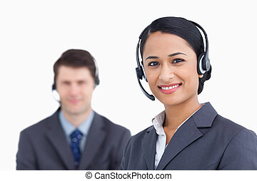Close up of smiling call center agents against a white...