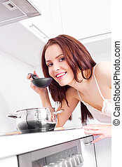 woman cooking dinner - beautiful young woman cooking dinner...