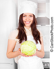 cook with cabbage - beautiful young cook with cabbage in the...