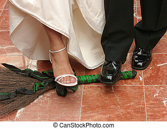 The feet of bride and groom jumping over the broom_a...