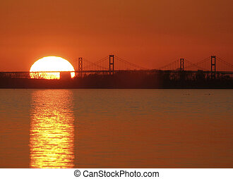 Chesapeake Bay Bridge with rising sun touching bridge -...