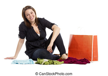 Young woman sitting on the floor with new clothes and shopping bag - Horizontal composition