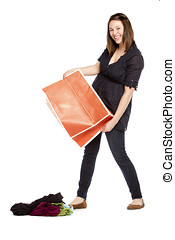 Shopaholic young woman dropping new dresses on the floor