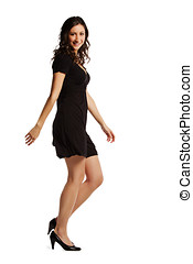 Full length image of confident young woman walking over...