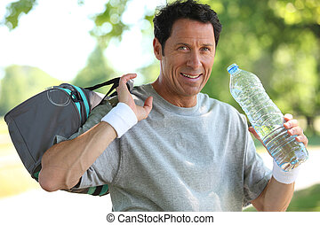 50 years old man drinking man after he did sport