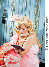 blond fashion princess woman reading ebook tablet with retro...