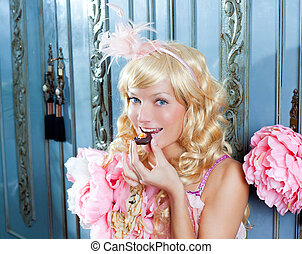 blond fashion princess woman eating chocolate at home with...