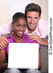 Interracial couple with a laptop