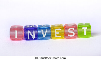 Text Invest on colorful wooden cubes over white