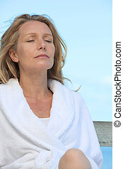 Woman in a bathrobe relaxing in the sunshine