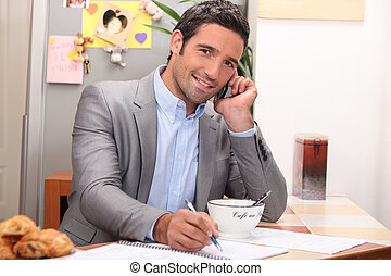 Man taking a business call over breakfast
