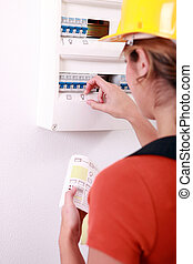 Female electrician putting icons on a fusebox