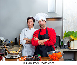 Chef couple man and woman posing in kitchen with uniform