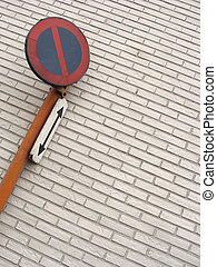 traffic sign in front of wall with white tiles