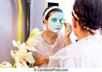 Funny housewife beauty green clay mask and cucumber at the...
