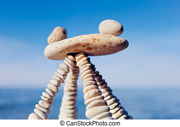 Equal Parts - Balancing of white stones on the top of...